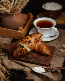 Croissants franceses com uma xícara de chá preto.