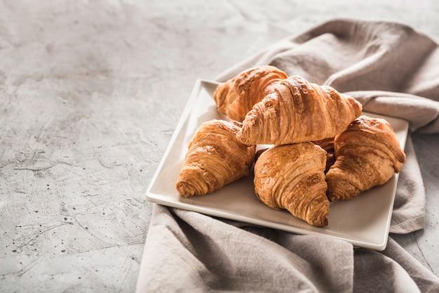 Croissants franceses recém-assados em um prato quadrado com um guardanapo cinza sobre uma mesa cinza clara.