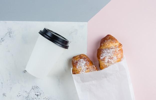 Croissants frescos com café para ir em um copo de papel no fundo tricolor. tire o café da manhã.