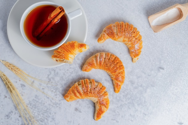 Croissants frescos com chá perfumado na superfície cinza.
