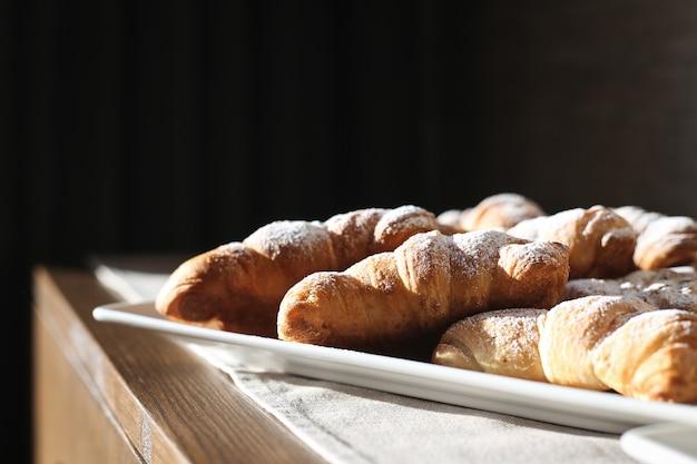 Croissants frescos com croissant com açúcar de confeiteiro em uma mesa de madeira