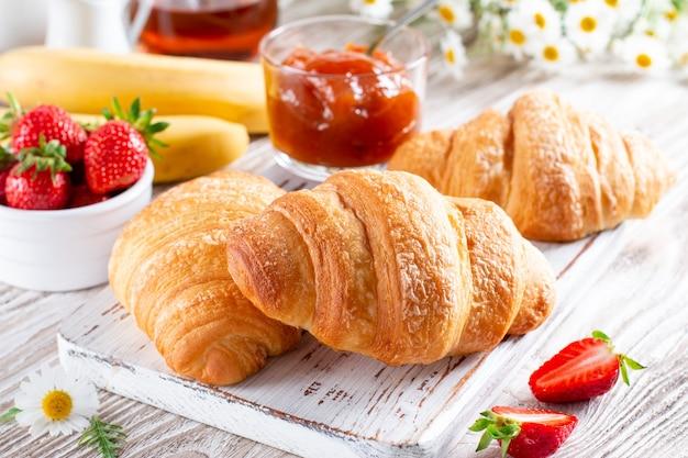 Croissants frescos com geleia no café da manhã na mesa de madeira