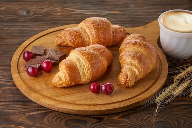 Croissants frescos com xícara de café na mesa de madeira
