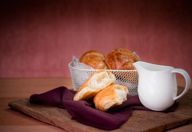 Croissants frescos deliciosos na cesta e no mel ou no leite branco do copo na tabela de madeira.