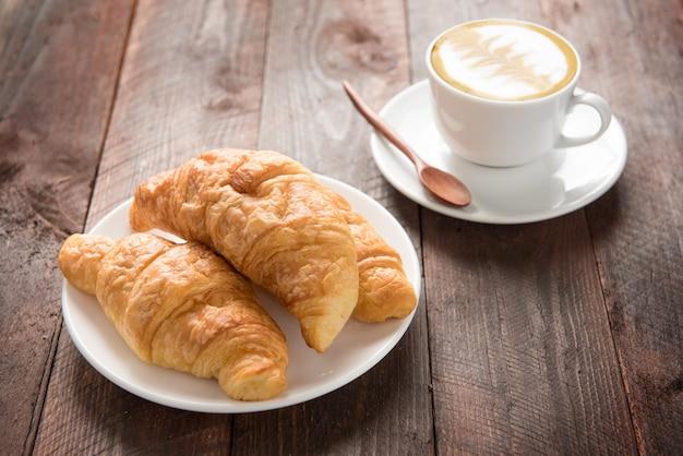 Croissants frescos e café na mesa de madeira