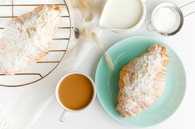 Croissants frescos em placas turquesas, leite e café na mesa branca