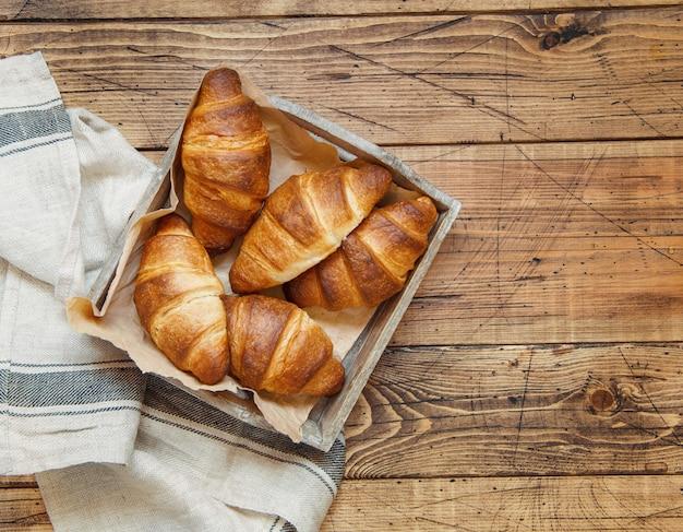 Croissants frescos em uma bandeja de madeira com um pano de prato em uma vista de mesa de madeira