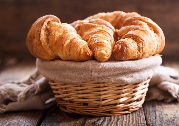 Croissants frescos em uma cesta sobre uma mesa de madeira