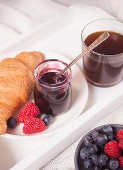 Croissants frescos, pães, frutas, geléia de groselha preta e copo de café. conceito de pequeno-almoço.