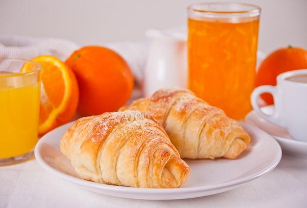 Croissants frescos, pães, laranjas, geléia de laranja e suco. conceito de pequeno-almoço.