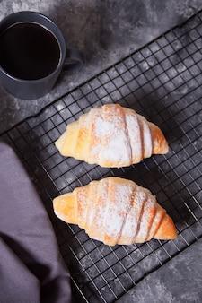 Croissants frescos pães na assadeira e xícara de café nas proximidades.