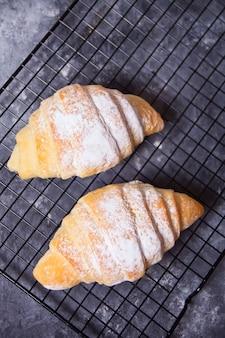 Croissants frescos pães na assadeira.