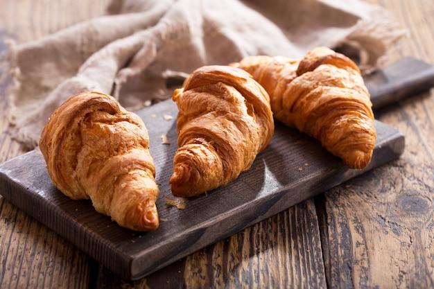 Croissants fresquinhos em uma tábua de madeira