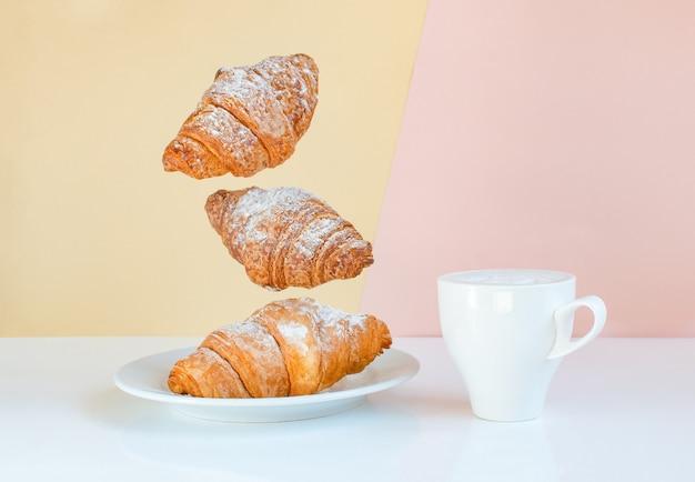 Croissants levitando em um prato com uma xícara branca sobre fundo amarelo e coral
