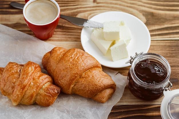 Croissants, manteiga e café em uma mesa de madeira