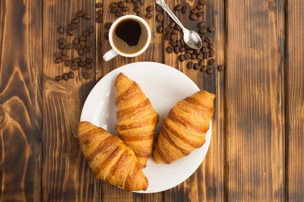 Croissants na chapa branca e café preto na xícara no fundo de madeira marrom. vista do topo. copie o espaço.