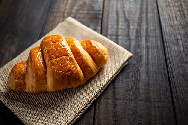 Croissants na mesa de madeira velha.