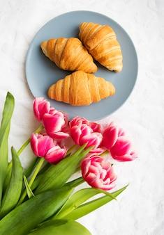 Croissants no fundo dos atacadores em um fundo branco com um buquê de tulipas cor de rosa