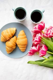Croissants no fundo dos cadarços com um buquê de tulipas cor de rosa, feliz dia