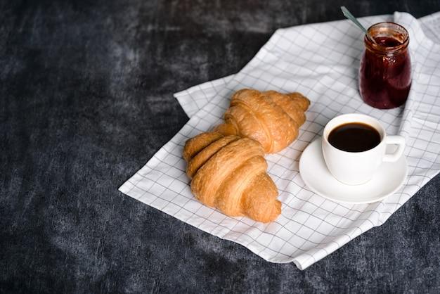 Croissants, panela com geléia e xícara de café à parte na mesa cinza