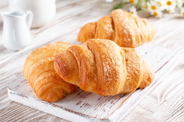 Croissants recém-assados em uma tábua de madeira leve