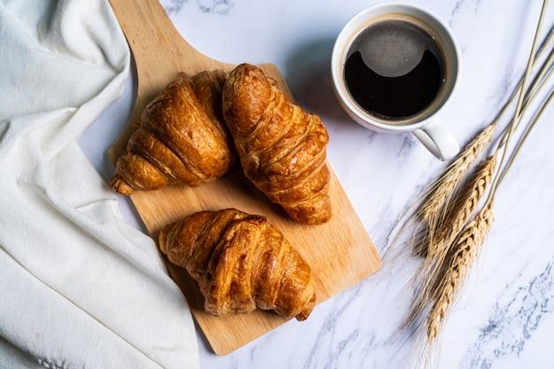 Croissants recentemente cozidos na tábua de madeira com café.