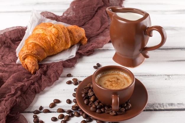 Croissants recentemente cozidos no guardanapo marrom, creme, às chávenas de café em uns pratos cerâmicos no fundo de madeira branco. doces frescos no café da manhã. deliciosa sobremesa. fotografia closeup. banner horizontal