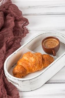 Croissants recentemente cozidos no guardanapo marrom, creme, às chávenas de café em uns pratos cerâmicos no fundo de madeira branco. doces frescos no café da manhã. deliciosa sobremesa. fotografia closeup. banner vertical.