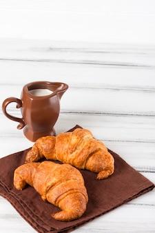 Croissants recentemente cozidos no guardanapo marrom, creme no jarro de leite cerâmico no fundo de madeira velho branco. doces frescos no café da manhã. deliciosa sobremesa. fotografia closeup. banner vertical.