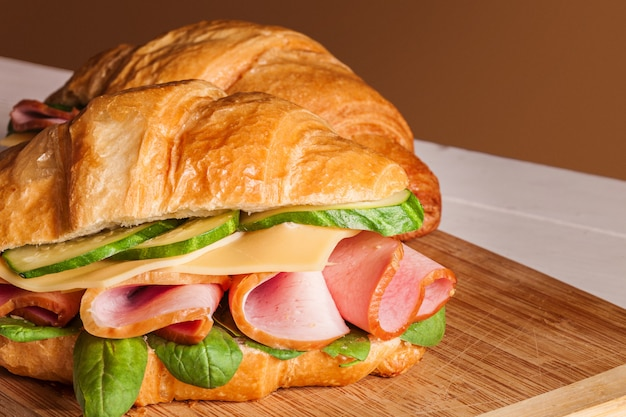 Croissants sanduíches na tábua de madeira