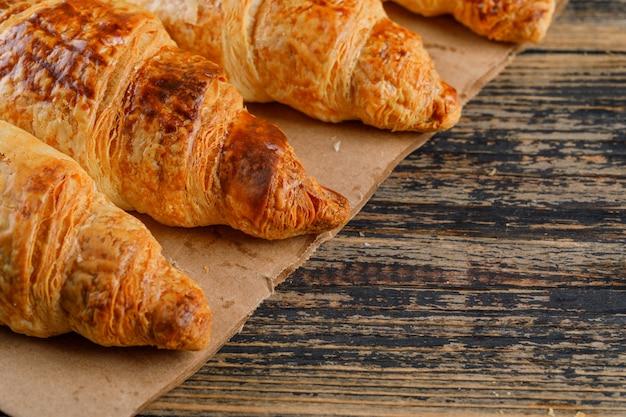 Croissants vista de alto ângulo em madeira e saco de papel