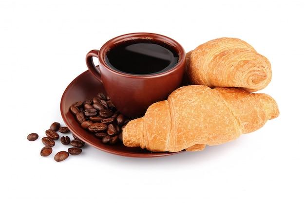 Croissants, xícara de café e feijão isolado no branco