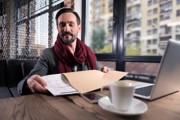 Cronograma de trabalho. homem bonito otimista e alegre olhando para o calendário e colocando-o no envelope enquanto se prepara para enviá-lo