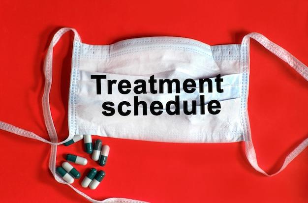 Cronograma de tratamento - texto em uma máscara protetora, comprimidos em um fundo vermelho