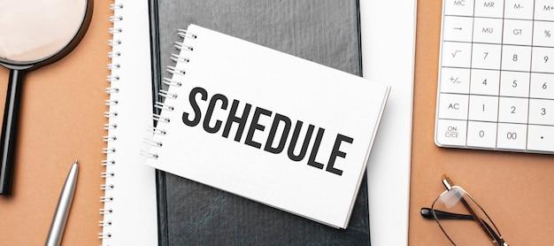 Cronograma no bloco de notas e vários papéis de negócios na superfície marrom