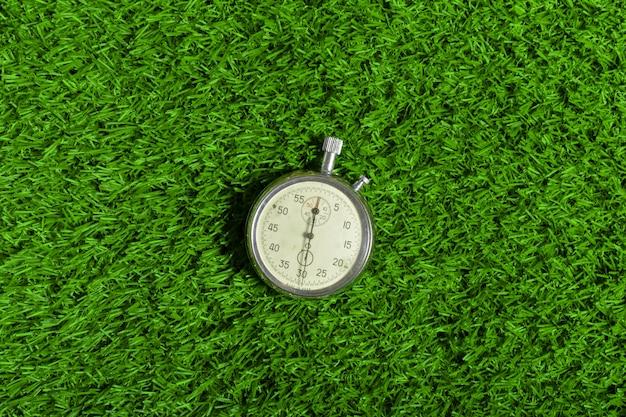 Cronômetro prateado na grama verde