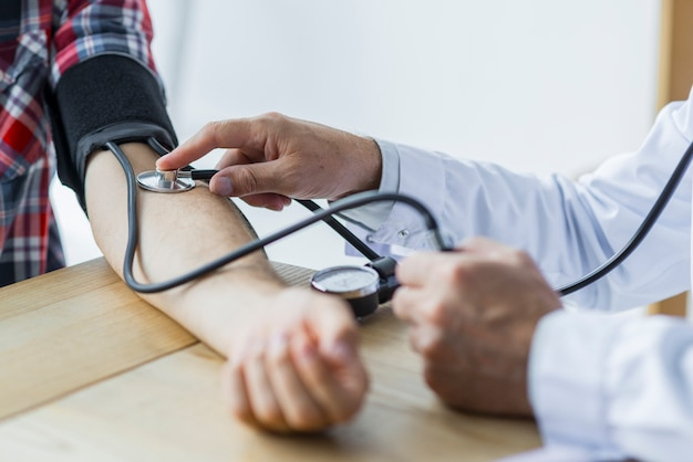 Crop doctor medindo a pressão arterial do paciente Foto Premium