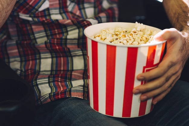 Crop homem comendo pipoca no cinema Foto gratuita