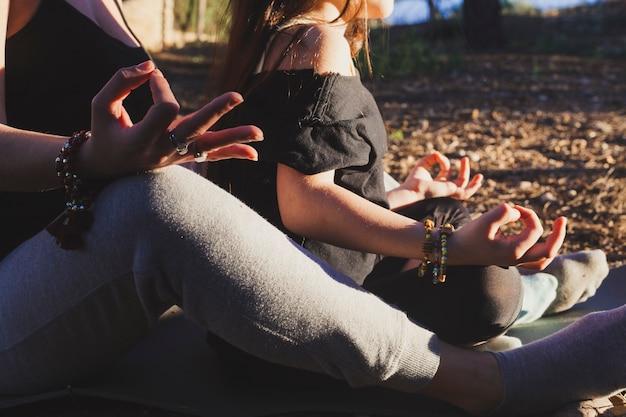 Crop mãe e filha meditando no parque