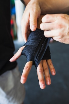 Crop sportsmen taping hand com elástico