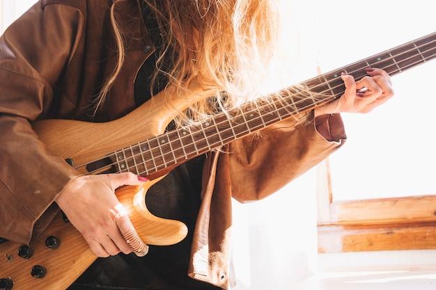 Crop woman playing guitar Foto gratuita