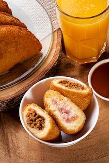 Croquete de carne frita com molho de pimenta e suco de laranja aperitivo brasileiro