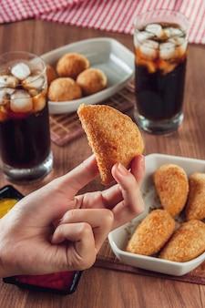 Croquete de rosbife frito com aperitivo brasileiro com dois copos de bebida