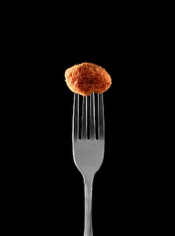 Croquete espinhoso no garfo com preto