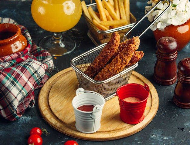 Croquetes de frango servidos com batata frita, maionese e ketchup