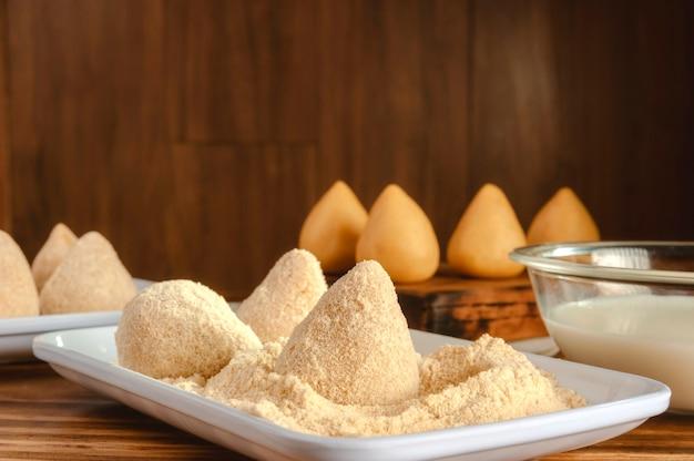 Croquetes empanados brasileiros crus em mesa de cozinha de madeira