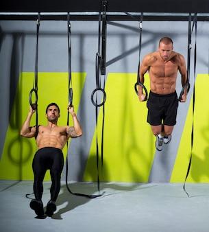 Crossfit dip ring dois homens treino no ginásio mergulhando