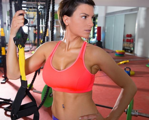 Crossfit fitness mulher de pé no ginásio segurando trx