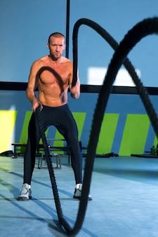 Crossfit lutando contra cordas no exercício de treino de ginásio