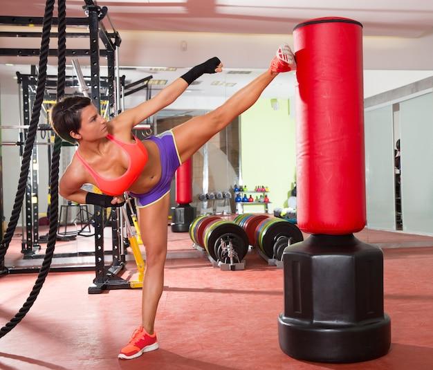 Crossfit mulher kick boxing com saco de pancadas vermelho